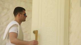 Стильный человек в форме с солнечными очками входит в спортзал на тропическом острове с полотенцем на его плече сток-видео