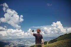 Стильный человек путешественника в шляпе держа телефон в горах Битник Стоковые Фото