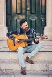 Стильный человек с бородой в рубашке и джинсах шотландки в улице на шагах около двери Мачо с красивой улыбкой сидит внутри стоковые фотографии rf