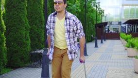 Стильный человек с ушибом на костылях идя в парк на солнечный день медленный mo видеоматериал