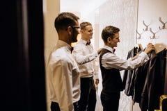 Стильный groom смеясь над и имея потехой с groomsmen пока getti Стоковые Фотографии RF
