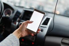 Стильный smartphone золота в руке девушки в автомобиле Стоковая Фотография RF