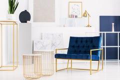 2 стильных таблицы рядом с креслом нефти голубым в ярком интерьере живущей комнаты современной квартиры стоковое фото rf