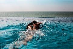 Стиль ползания заплывания молодой женщины в бассейне с видом на море и голубым небом стоковое изображение