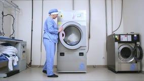 Стиральная машина загрузки женского работника на прачечной гостиницы Коммерчески прачечная сток-видео