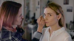 Стилизатор девушки работая в студии красоты Компенсируйте красивую блондинку Работа с тенью акции видеоматериалы