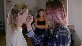 Стилизатор девушки работая в студии красоты Компенсируйте красивую блондинку Работа с тенью сток-видео