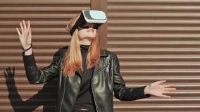 Стильная девушка в виртуальных стеклах приближает к горизонтальным коричневым занавесам сток-видео