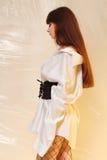 Стильная девушка в модных одеждах на предпосылке просвечивающего фильма Стоковая Фотография RF