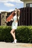 Стильная девушка в представлениях солнечных очков с longboard Стоковые Фото