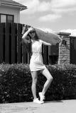 Стильная девушка в представлениях солнечных очков с longboard Стоковое Изображение