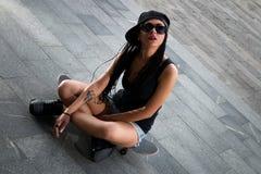 Стильная девушка в сексуальных шортах сидя на скейтборде на плитке Стоковые Изображения