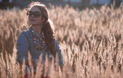 Стильная девушка на поле в солнце излучает Стоковая Фотография RF