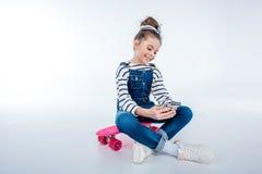 Стильная жизнерадостная девушка сидя на скейтборде и используя smartphone Стоковая Фотография RF