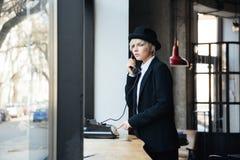Стильная красивая девушка используя телефон в кафе Стоковое Изображение