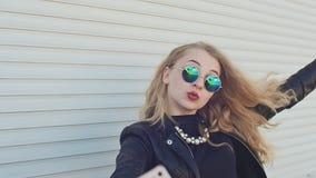 Стильная молодая блондинка в кожаной куртке и солнечных очках принимает фото от мобильного телефона около горизонтального ролика сток-видео