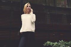 Стильная молодая женщина остановила перед большими окнами дорого стоит ресторана, ждать ее парня Стоковые Изображения
