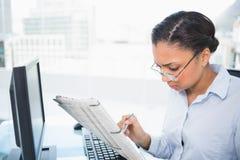Стильная молодая темная с волосами коммерсантка читая газету Стоковое Изображение RF