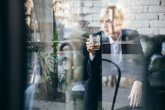 Стильная довольно белокурая девушка держа стекло питья спирта Стоковое фото RF
