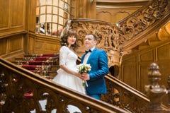 Стильная роскошная невеста и красивый элегантный groom представляя держащ руки с букетом на старых деревянных лестницах Стоковые Фотографии RF