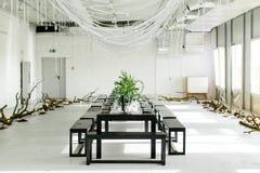 Стильная таблица, просторная квартира Комната дизайна в стиле просторной квартиры Черная таблица, стулья, блюда, свечи Опарникы с Стоковое фото RF
