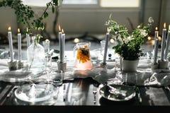 Стильная таблица, просторная квартира Комната дизайна в стиле просторной квартиры Черная таблица, стулья, блюда, свечи Опарникы с Стоковое Фото