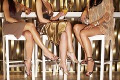Стильно одетые женщины сидя на баре стоковые фотографии rf