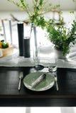 Стильные еды и длинная таблица, просторная квартира Черная таблица, стулья, блюда, свечи Банки с зелеными цветами, цветки черные  Стоковая Фотография