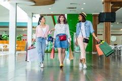 Стильные молодые женщины идя с хозяйственными сумками, концепцией маленьких девочек ходя по магазинам Стоковые Изображения