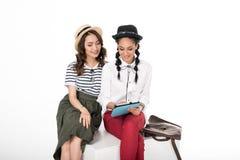 Стильные молодые женщины сидя совместно и используя цифровую таблетку Стоковое Изображение RF