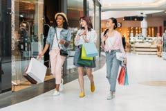 Стильные молодые усмехаясь женщины идя с хозяйственными сумками Стоковое фото RF