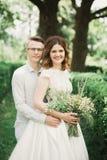 Стильные пары счастливых новобрачных идя в парк на их день свадьбы с букетом Стоковая Фотография