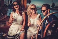 Стильные состоятельные друзья имея потеху на роскошной яхте стоковые изображения rf