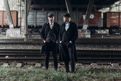 Стильные люди гангстеров, представляя на предпосылке железной дороги Англия в теме 1920s модная зверская уверенно группа атмосфер стоковое фото rf