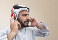 Стильный аравийский человек в наушниках, аравийский парень слушая к музыке Стоковое Изображение