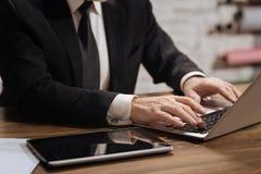 Стильный бизнесмен печатая на компьтер-книжке Стоковые Фото