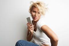 Стильный женский делая Smartphone Selfie пока стоящ против наушников музыки белой предпосылки слушая скопируйте космос Стоковые Фото