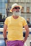 Стильный зрелый бородатый человек в ярких желтых футболке и шляпе Стоковое фото RF