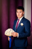 Стильный красивый темный с волосами groom держа букет свадьбы в руках стоя в фиолетовом интерьере Стоковое фото RF