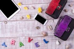 Стильный Модное Lady& x27; аксессуары s Роскошные сумки кожи питона, косметики, таблетка, smartphone, plumeria цветут Стоковые Фотографии RF