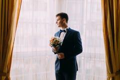 Стильный молодой темный с волосами groom держа букет свадьбы бледного - розовые розы в руках стоя около окна Стоковое Изображение RF