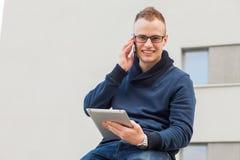 Стильный парень соединился на интернете с таблеткой и мобильным телефоном в городке Он счастлив Стоковые Изображения