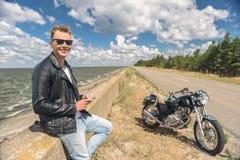 Стильный парень стоя рядом с его мотоциклом Стоковая Фотография