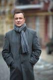 Стильный человек в сером пальто с scraft на стоковые изображения rf