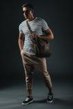 Стильный человек в солнечных очках держа коричневую кожаную сумку и представляя в студии стоковые фотографии rf