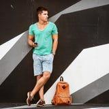 Стильный человек моды путешествуя с сумкой стоковое фото