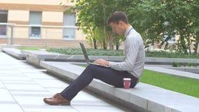 Стильный человек работая на компьтер-книжке outdoors, терраса, чашка кофе акции видеоматериалы