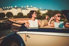 2 стильных дамы в классическом автомобиле с откидным верхом Стоковое Фото