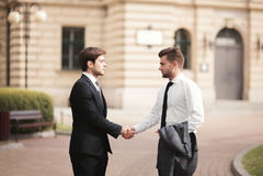 2 стильных бизнесмена тряся руки в костюмах Стоковое Фото