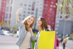 2 стильных девушки с хозяйственными сумками Стоковое Изображение